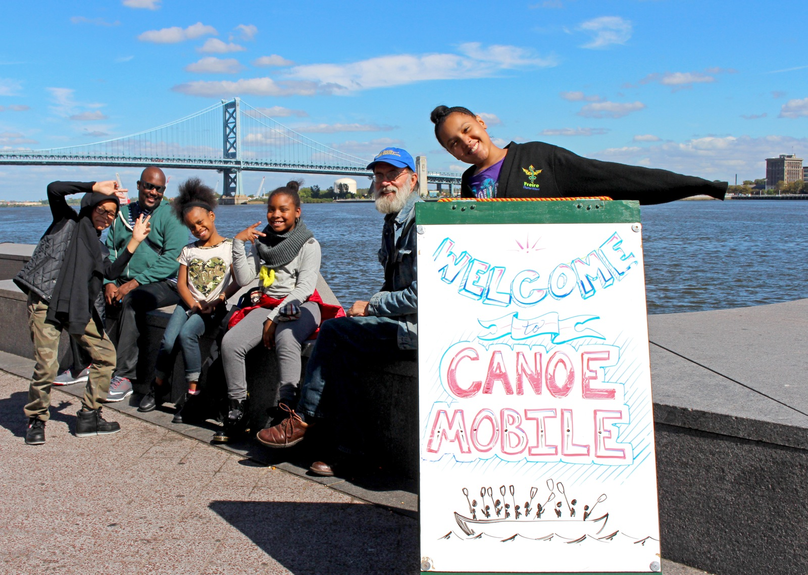 6 participants smile for the camera next to the Canoemobile sign by the river in Philadelphia