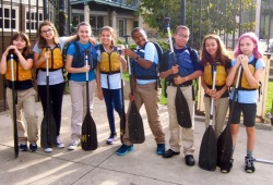 group photo of youth on land with their life jackets and paddles ready