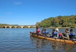 participants paddle their canoe on a calm river on a sunny day in Philadelphia