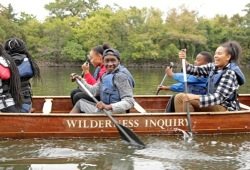 an action shot of youth paddling their canoe along the river