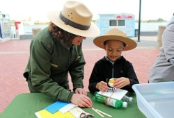 a young boy works on a craft outside with a park ranger