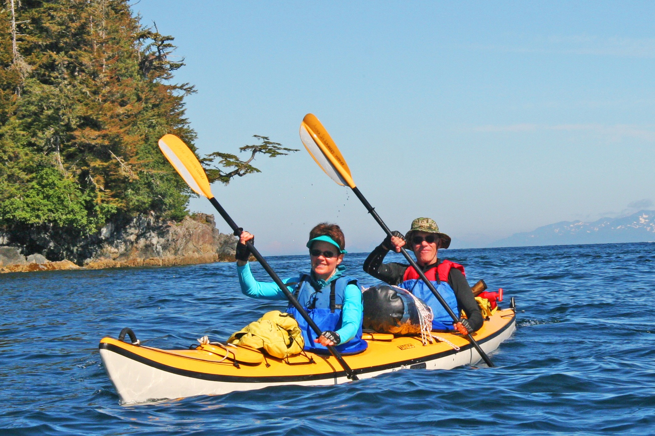 A Couple In Tandem Sea Kayak On Deep Blue Water Near Rocky Island With