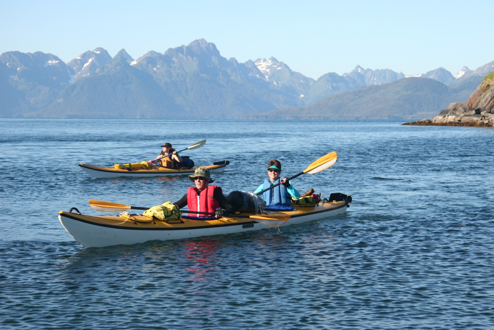 Sea kayaks paddle near Chenega Island in Prince William Sound with mountains in the background.