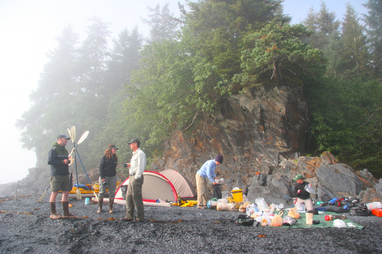 Morning fog rolls through a campsite in Prince William Sound while participants eat breakfast and pack up gear.