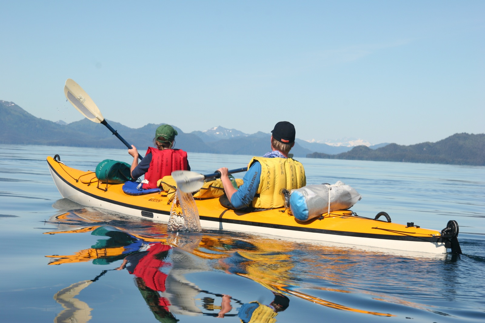 Two People In A Tandem Sea Kayak On The Calm Water Prince William Sound Surrounded