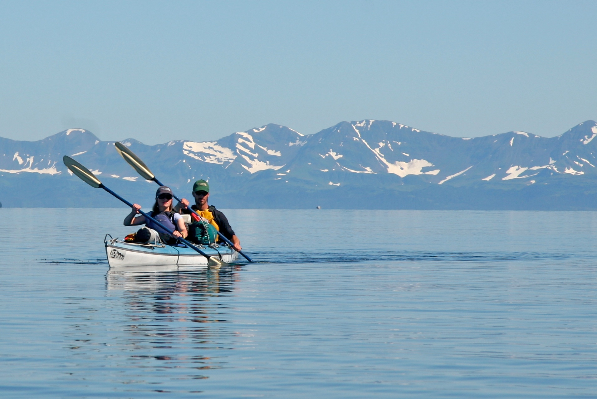 Two people in a blue and white tandem sea kayak with mountains in the background.