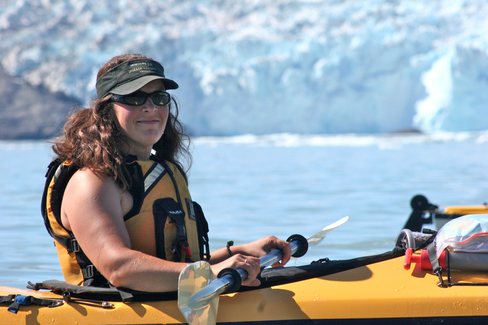 A woman takes a break from sea kayaking at a safe distance from the ever moving Chenega Glacier.