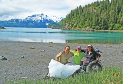 Three participants, one using a wheelchair, pose behind a large chunk of ice on the beach of Jackpot Bay with impressive mountains in the background.
