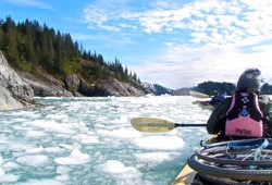 Two kayaks, one with the wheels of a wheelchair strapped to the middle, paddle through chunks of ice in the water as they make their way along the shore.