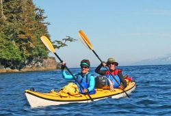 A couple in a tandem sea kayak on deep blue water near a rocky island with mountains in the background .