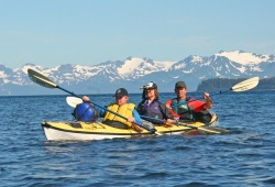 Three people paddle a yellow sea kayak with snowcapped mountains in the background.