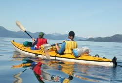 Two people in a tandem sea kayak on the calm water in Prince William Sound surrounded by mountains in the distance.