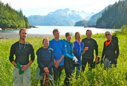 Seven participants pose in long green grass with an amazing view of the lake with  snow capped mountains in the back at Gaamak Bay.