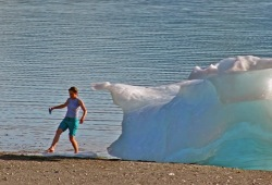 A woman dips her toes in the cold water off the beach at Gaamak Cove next to a giant piece of ice.