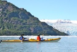 A yellow tandem sea kayak paddles the chilly waters of the Nassau Fjord to get a better look at the Chenega Glacier.