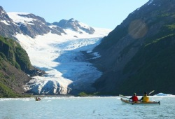 Two tandem sea kayaks paddle towards an inlet near Tiger Tail Glacier.