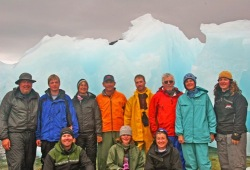 The group of 11 poses in front of large pieces of blue ice in Prince William Sound.