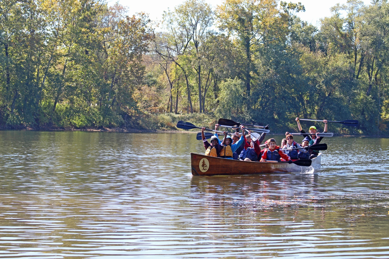 group of participants hold their paddles above their heads while canoeing in Reading