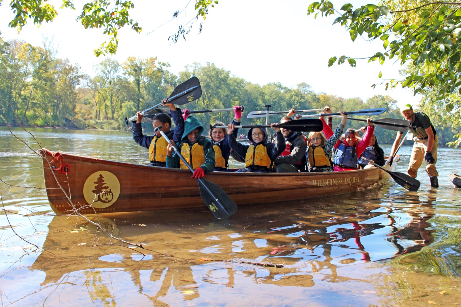 A Group of youth get ready to launch off the shore in the voyageur canoe