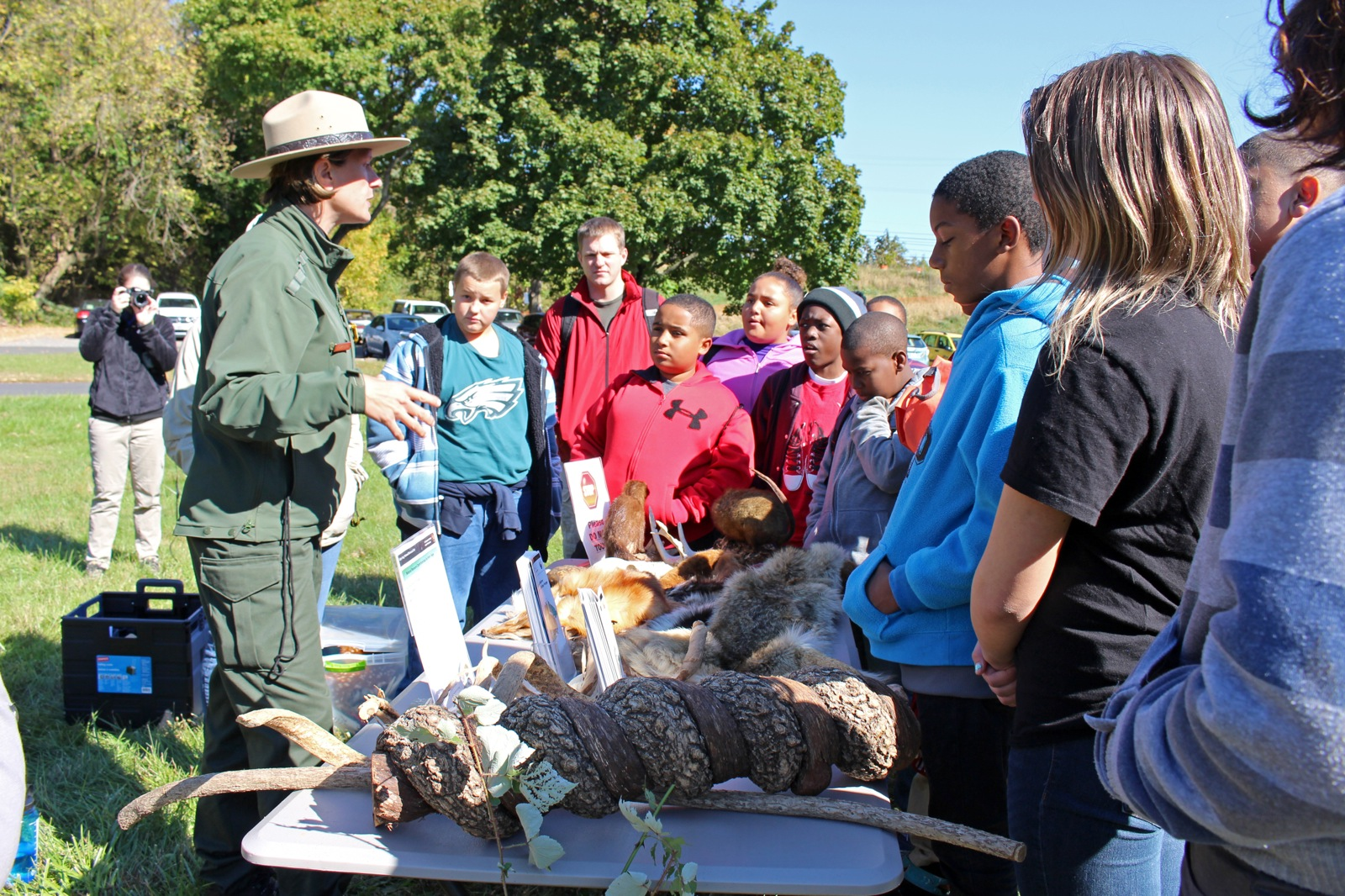 a group of youth stand around a display table with different animal hides as they learn about wildlife