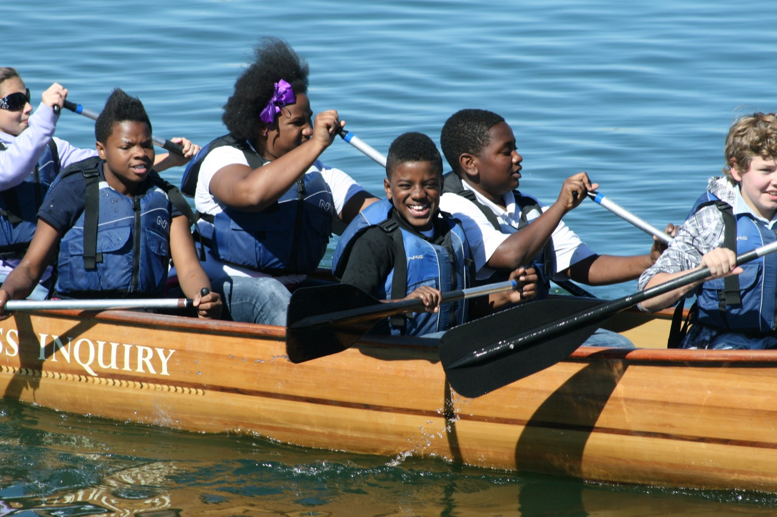 an action shot of 6 youth helping paddle the voyageur canoe on Trail Creek Lake