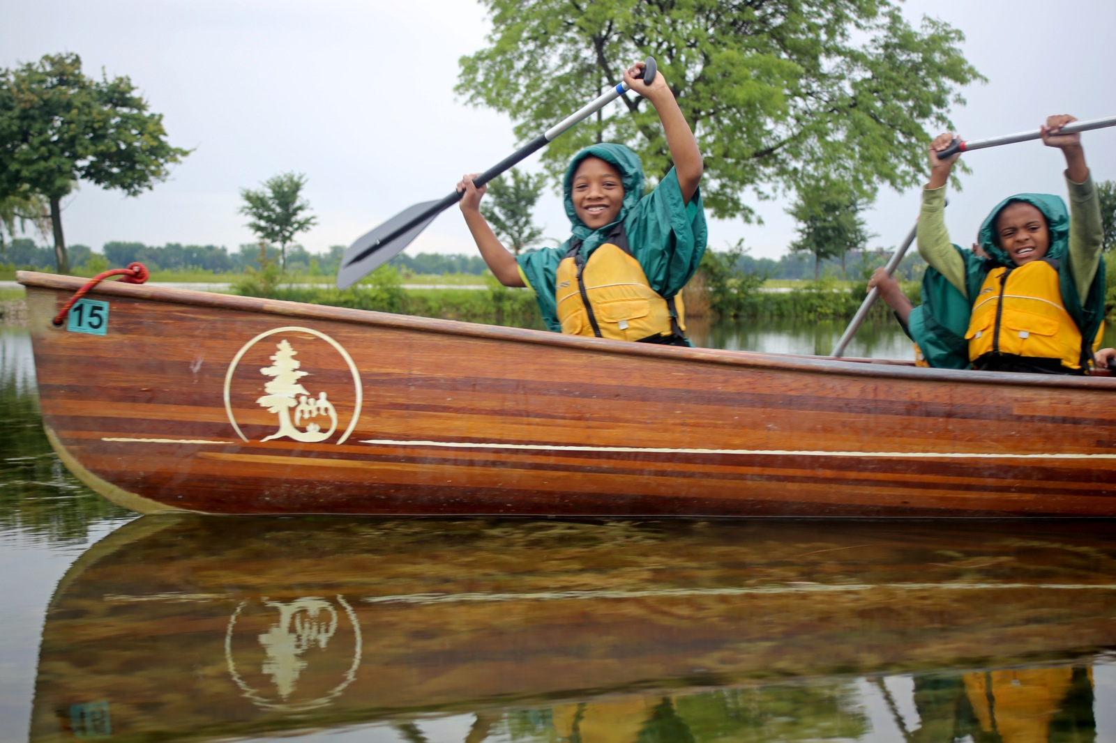 two young boys in the front of the canoe hold their paddles high on a cloudy day