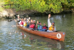 canoemobile members wave and smile to the camera while paddling along the river