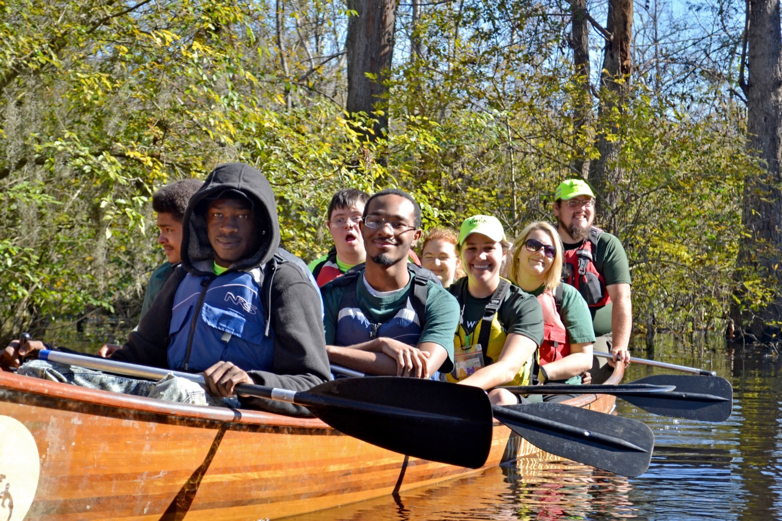 staff members and participants smile for the camera as they take a break from paddling the canoe
