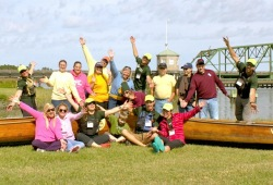 Group of participants pose next to the canoes in front of the Savannah River