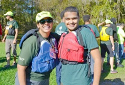 a staff member and participant pose for a photo together with their life jackets on