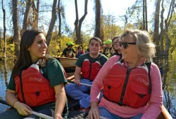 two participants sit next to each other in the voyageur canoe