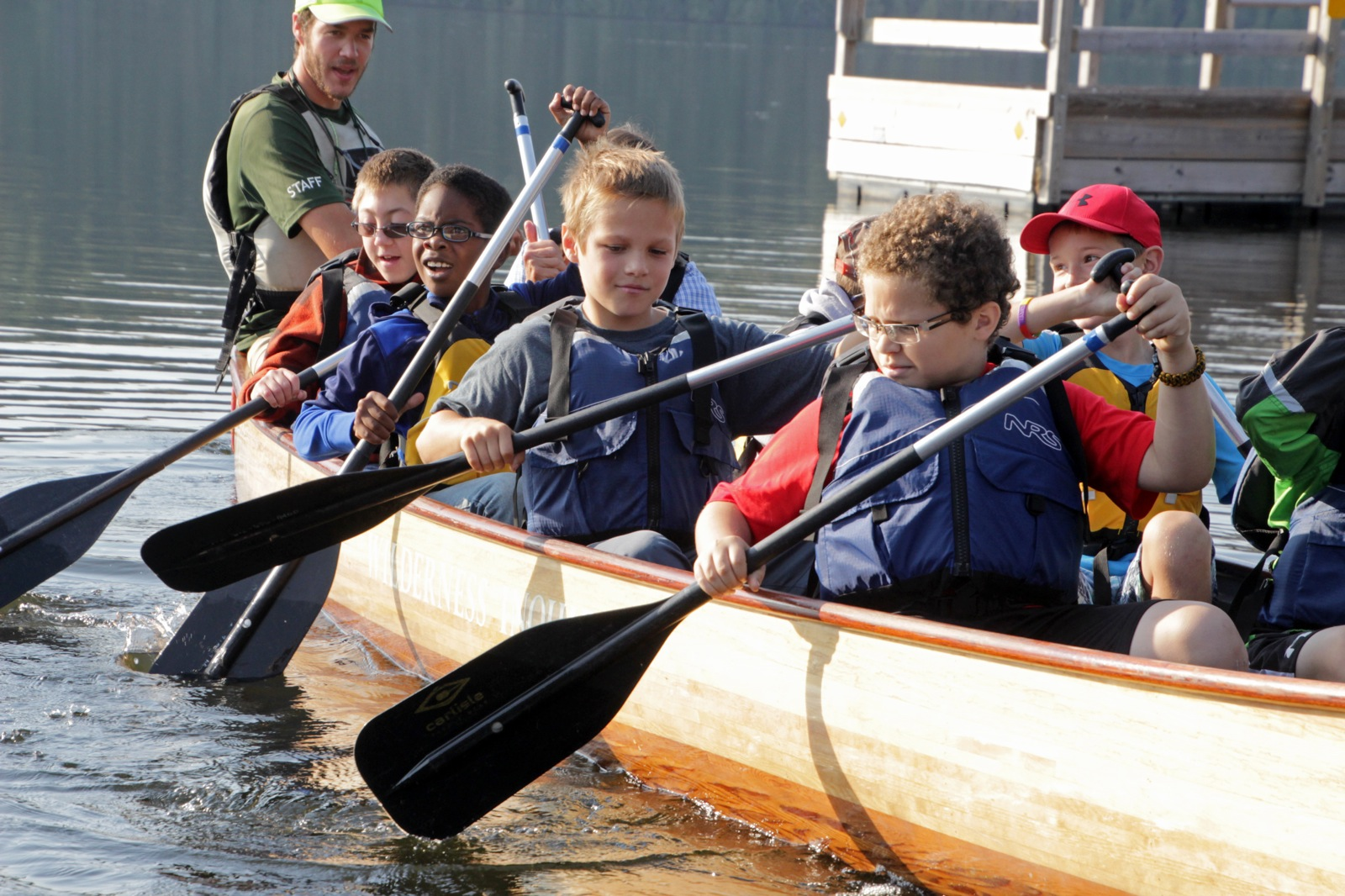 a group of youth work together to paddle the voyageur canoe along the lake