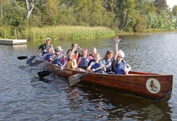 a group of youth paddle away from shore in a Voyageur canoe