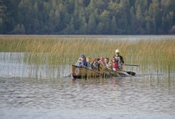 a group of participants paddle the canoe  through vegetation in the water