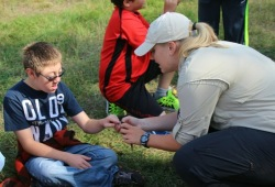 a boy learns about wildlife as a staff member passes around an object