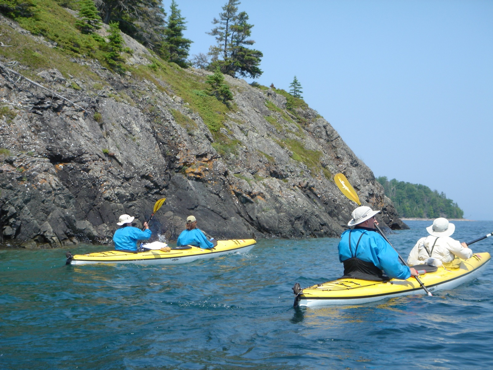 Two tandem sea kayaks paddle around the rocky shore of Shell Island on a sunny day.