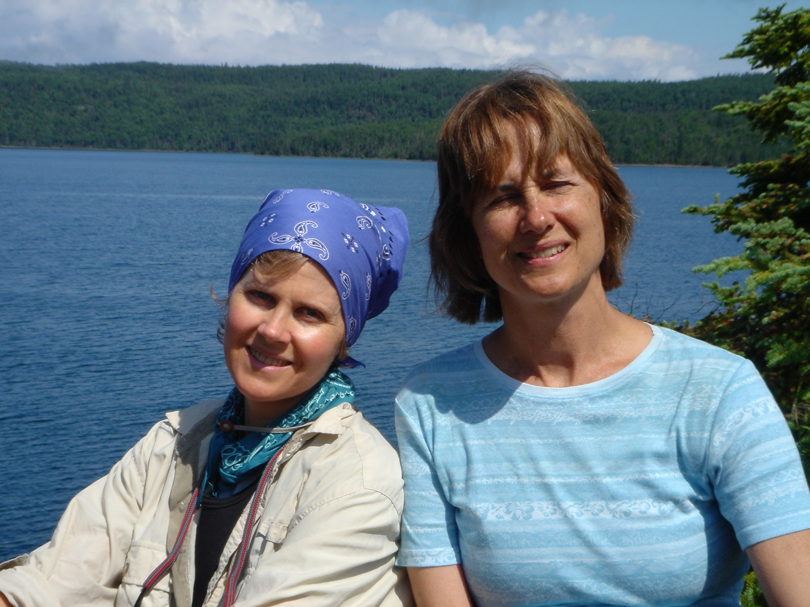 Two women smile in front of Lake Superior on the Slate Islands Sea Kayak Expedition.