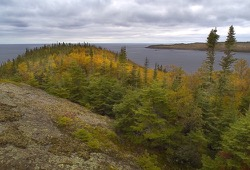 Beautiful view from Slate Islands on Lake Superior of large rocks and fall foliage near the lake.