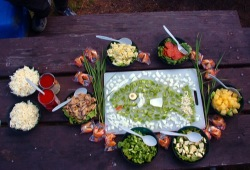 Food is laid out on a picnic table with a mosaic of shopped vegetables in the shape of a fish in the center of all the bowls.