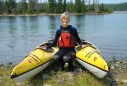 A woman poses next to two yellow sea kayaks on the shore of Pearl Island.