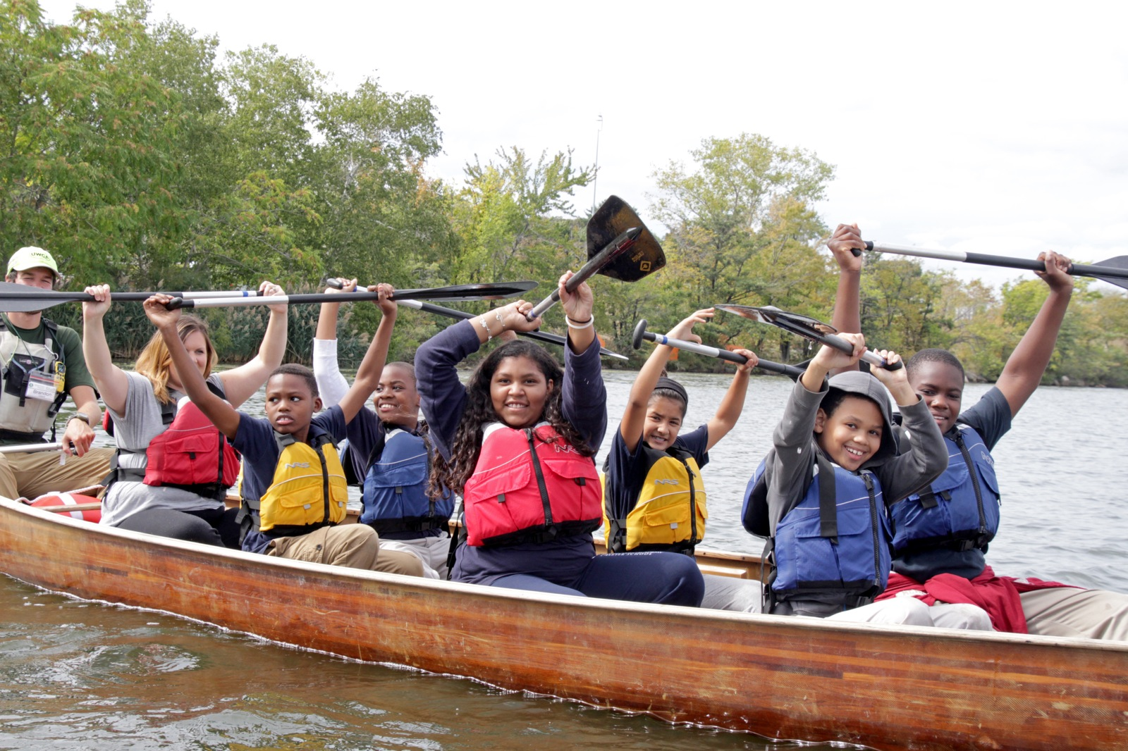 participants in a Voyageur canoe hold their paddles above their heads taking a break from paddling