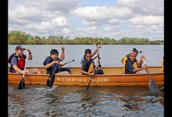 action shot of participants using their paddling techniques in the canoe
