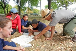 a park staff member assists four participants find a location on a map