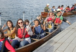 A group of participants push off the canoe from the dock ready to paddle the River