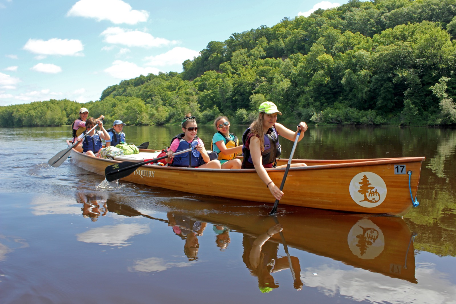 Four girls and two Wilderness Inquiry guides paddle a Voyageur canoe on a glassy St. Croix River on a sunny afternoon.