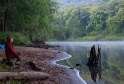 A woman sits on a log and relaxes on the shore of the St. Croix River on a misty morning.