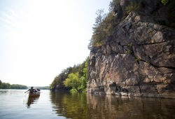 A Voyageur canoe paddles past rocky cliffs on the edge of the river.