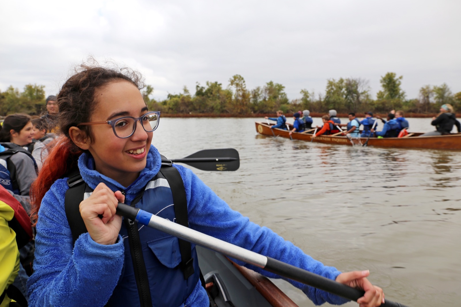 A happy student paddling on the water