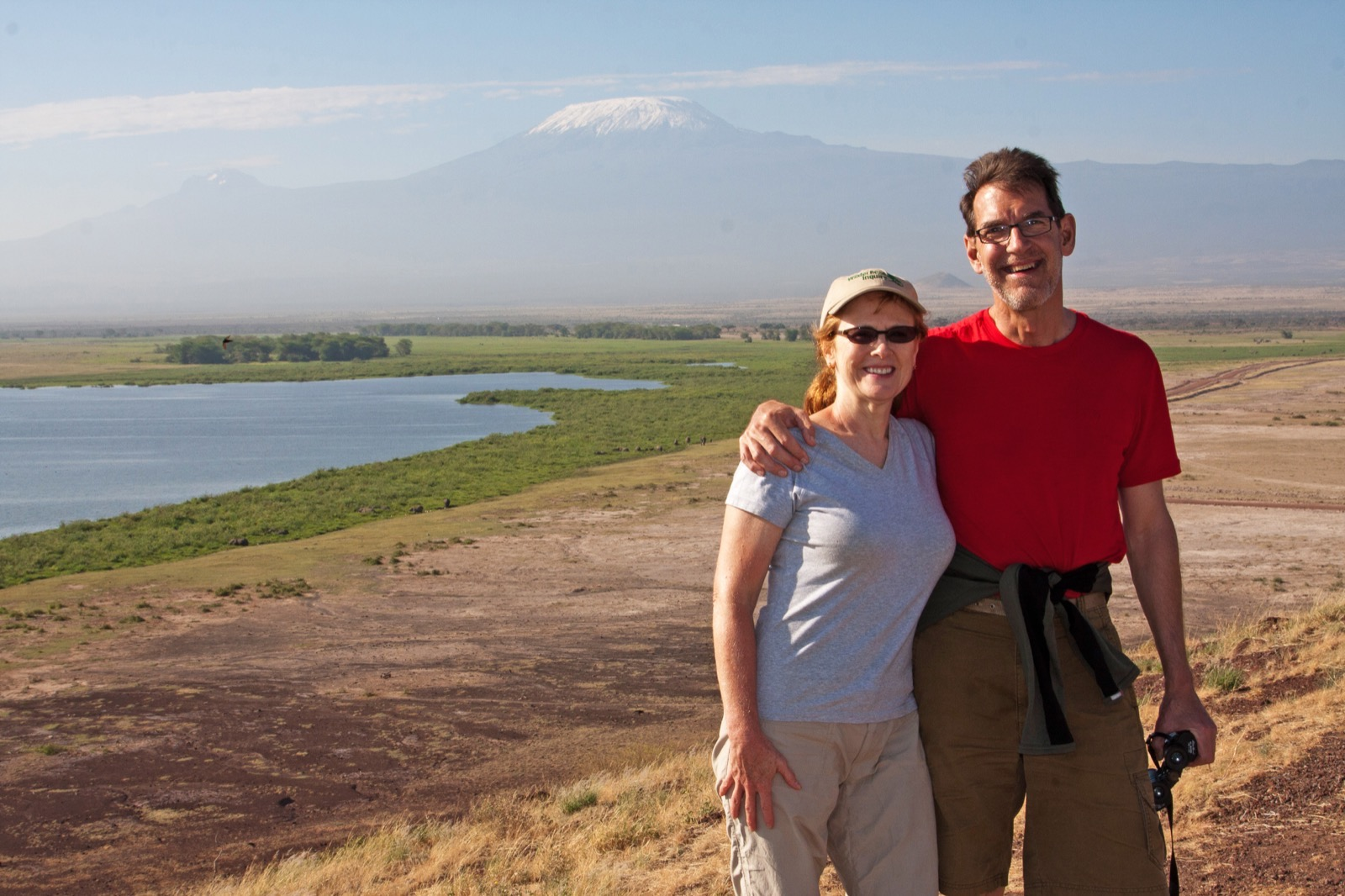 A couple poses with Mt. Kilimanjaro in the distance.