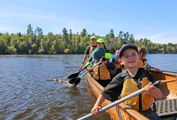 A student from Tower paddles in a Voyageur canoe.